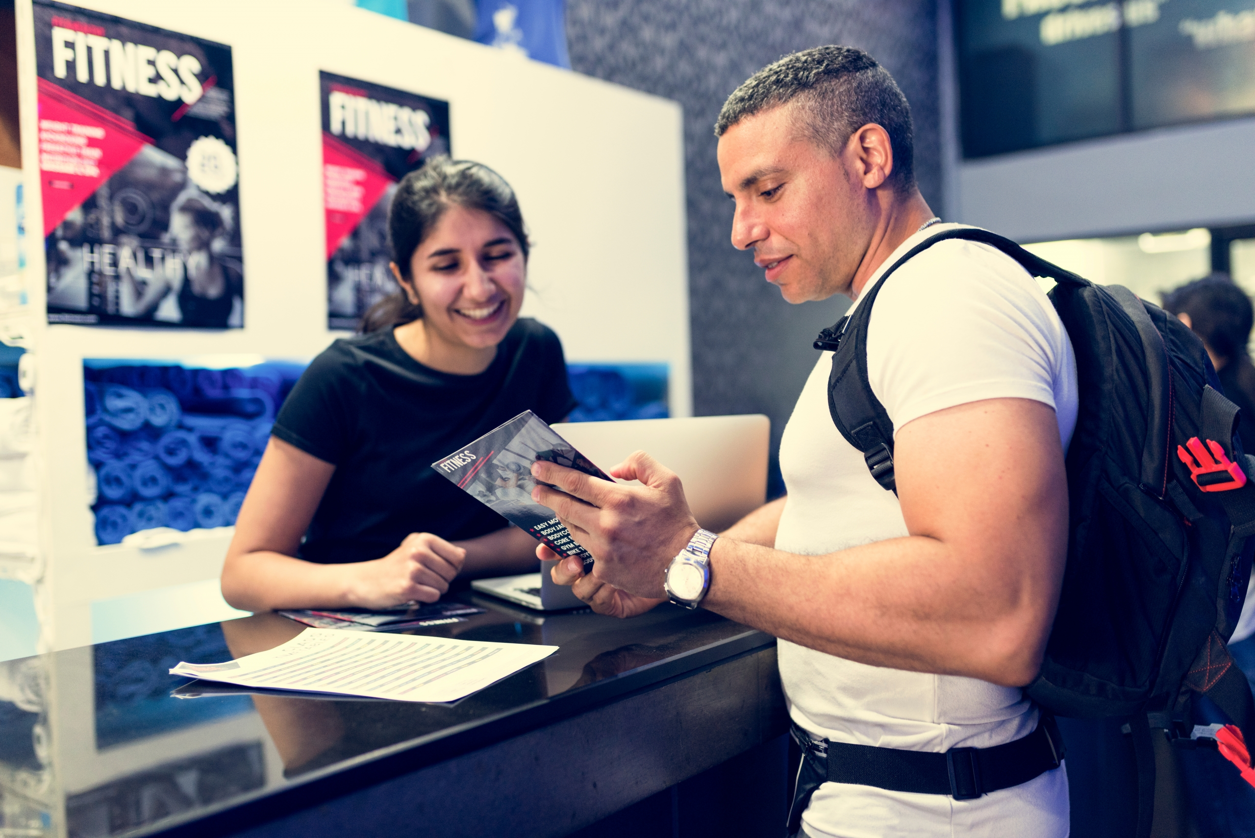 Man And Woman Discussing Membership At A Gym - Business Solutions